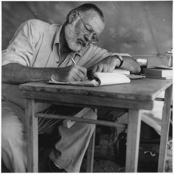 Ernest_Hemingway_Writing_at_Campsite_in_Kenya_-_NARA