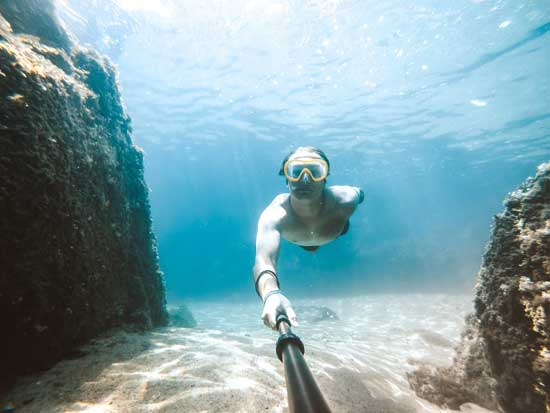 Man snorkeling and taking a selfie photo
